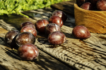 Vintage plums in a wooden bowl, on a wooden background, on the grass on a sunny afternoon on the grass.