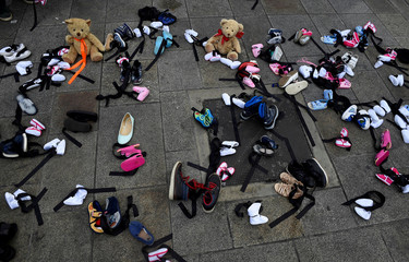 Children's shoes and toys are left on the pavement as part of a protest during the visit of Pope Francis to Dublin