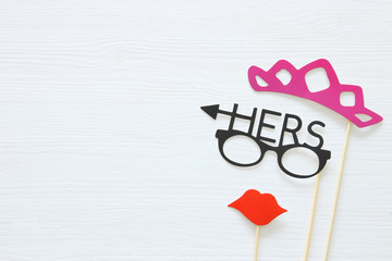 Top view image of funny photo booth props with text: HERS for party or wedding over white background.