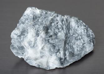 Specimen of mineral magnesite on gray background