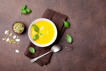 Autumn vegetable or pumpkin soup in white bowl on stone kitchen table top view.