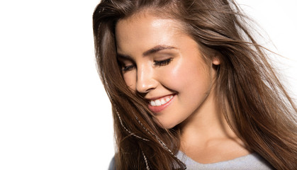 Close up portrait of cheerful girl with beautiful long hair posing at studio. Happy laughing brunette with delicate make-up and fresh clean skin looking down. Isolated on grey background
