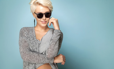 Portrait of fashionable blonde in trendy grey shirt posing in sunglasses. Young smiling female with beautiful short fair hair. Copy space in right side. Isolated on blue background