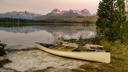 Sawtooth Mountains of Idaho with a canoe parked on the shore of a lake