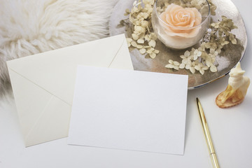 Elegant feminine stationery mockup scene with a blank paper greeting card, golden accessories, candle and flowers, on white background