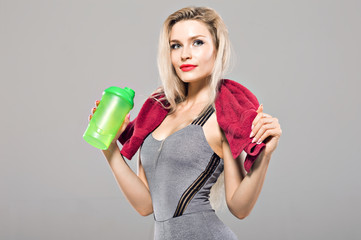 Charming model posing in the studio with a shaker in her hands and a towel around her neck