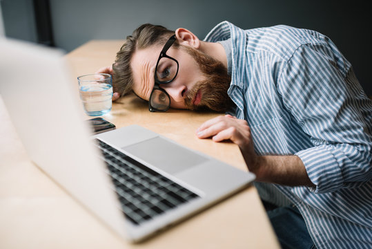 Young bearded hipster using laptop computer, he feeling sick. Depression. Tired. Stress. Freelancer planning project, deadline. Frustrated businessman sitting in loft office