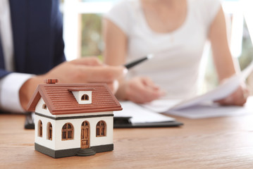 House model and real estate agent working with client in office, closeup