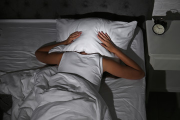 Young woman covering head with pillow in bed at home. Sleep disorder