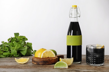 Bottle and glass with natural charcoal lemonade on table against light background