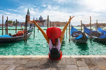 Glückliche Touristin mit rotem Hut genießt die Aussicht auf die Gondeln vom Markusplatz in Venedig, Italien  Fototapete