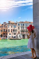 Attraktive, webliche Touristin im weißen Kleid schaut auf den Kanal Grande in Venedig an einem sonnigen Tag, Italien