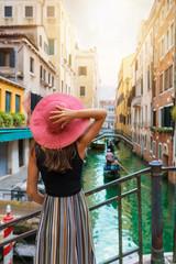 Elegante Frau mit rotem Sonnenhut schaut auf einen Kanal mit vorbeifahrender Gondel in Venedig, Italien