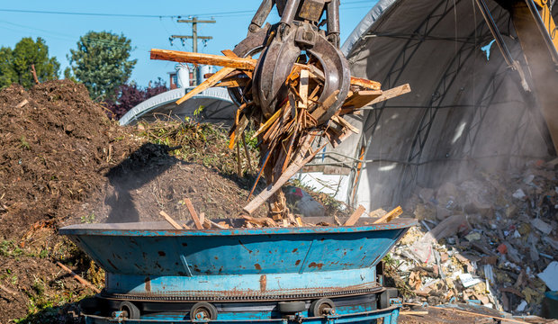 A machine grapple dopes construction waste into grinder to be recycled into wood chips.