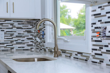 Faucet and kitchen sink with brick wall