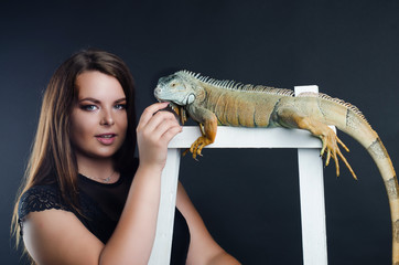perfect portrait girl and big green iguana in the studio