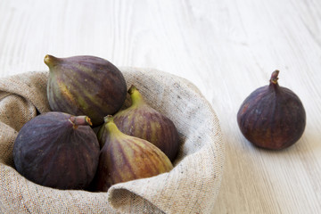 Fresh figs in a bowl on a white wooden surface, side view. Close-up.