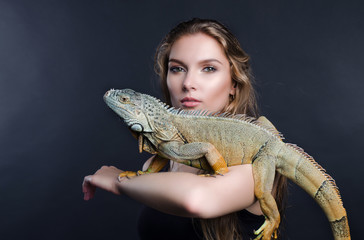 perfect portrait beautiful girl and green iguana in the studio