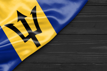 Flag of Barbados and place for text on a dark wooden background