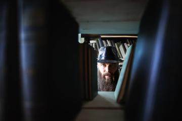 Bearded man spying through bookshelves
