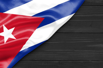 Flag of Cuba and place for text on a dark wooden background