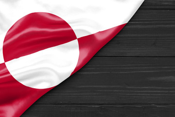 Flag Greenland and place for text on a dark wooden background