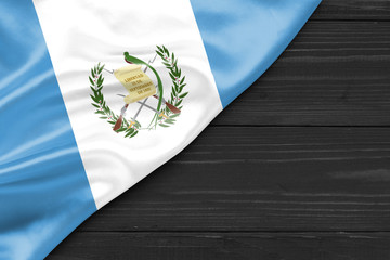 Flag of Guatemala and place for text on a dark wooden background
