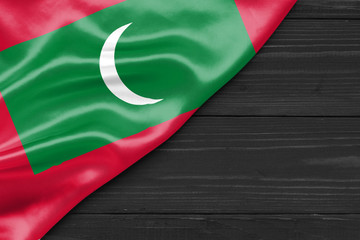 Flag of the Maldives and place for text on a dark wooden background