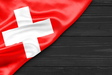 Flag of Switzerland and place for text on a dark wooden background