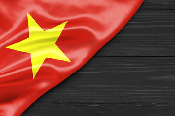 Flag of Vietnam and place for text on a dark wooden background