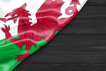 Flag of Wales and place for text on a dark wooden background