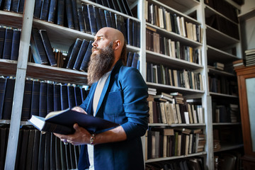 Stylish bearded man with book in library