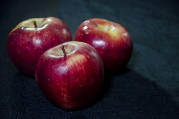 Tres manzanas rojas sobre un mantel negro