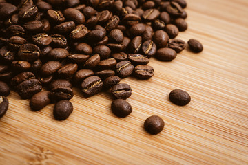Coffee beans roasted on a wooden table with much of beans with a great aroma