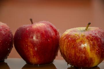 Tres manzanas mojadas sobre fondo rojo
