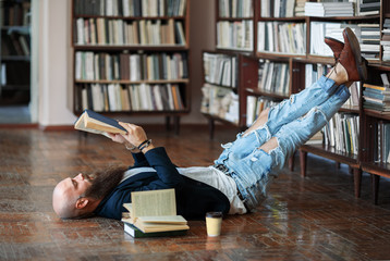 Bearded hipster man relax and reading book lies on the floor