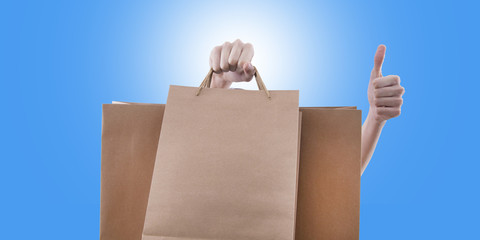 hand with shopping bags and sign of okay and satisfaction