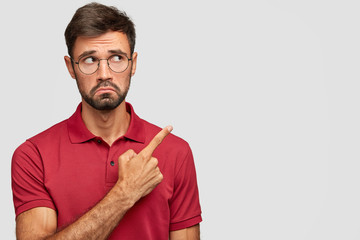 Displeased scientist with dark bristle, makes dislike grimace, points at upper right corner, expresses antipathy to item, dressed in casual red t shirt. People, emotions and advertisement concept