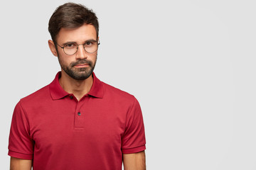 Attractive self confident hipster looks directly at camera with serious expression, wears round spectacles and red t shirt, stands against white background with copy space for your slogan. Masculinity