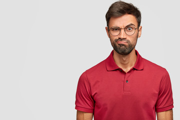 Angry person with sullen surprised expression, purses lips, raises eyebrows in bewilderment, being unshaven, stands against white background with copy space for advertisement. Facial expressions
