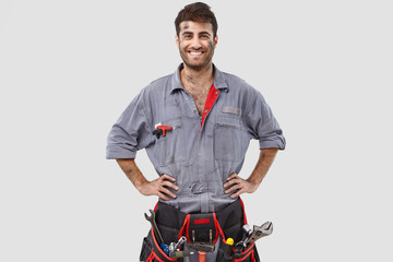Buoyant successful handyman wears grey overalls, tool belt, stands with hands on waist over white background has shining smile. Content industrial worker rejoices coming weekend after hard working day