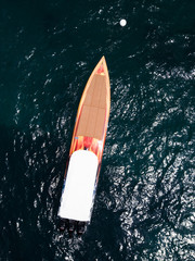 Aerial view of a beautiful orange racing boat sailing on a transparent and turquoise sea. Sardinia, Italy.