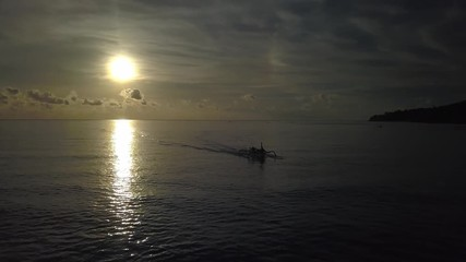 Wall Mural - Morning flight over calm sunrise ocean water with moving asian indonesian boat