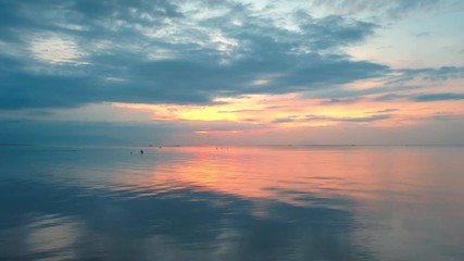 Wall Mural - Camera moving right over calm reflected ocean water with colorful sunset cloudy background in skyline