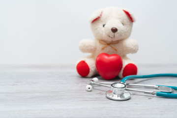 Close up Plush Teddy Bear with Stethoscope Device on Top of a Glass Table, Emphasizing Copy Space.