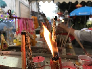Focus at flame of red candle at shrine, background is blurred that is people is sticking incense.