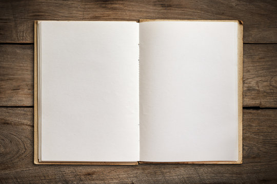 Open old book on vintage wood background.