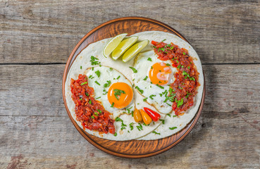 Mexican cuisine. Breakfast huevos rancheros on a wooden table. The view from the top. Copy-space.