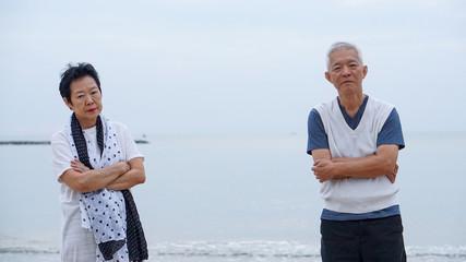 Asian elderly couple fight upset at ocean sea beach morning