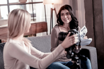 Communication. Glad dark-haired woman smiling while her friend fixing the camcorder